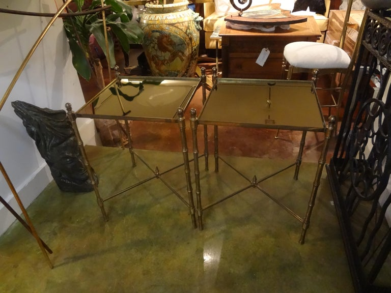 Lovely pair of French faux bamboo brass tables with bronze mirrored tops. This great pair of tables or gueridon are in the style of Maison Jansen or Maison Baguès and date to the 1940s. These Hollywood Regency brass tables are perfect as side