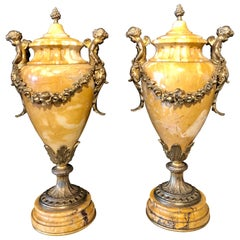 Pair of French Bronze and Marble Cassolettes Each with Cherubs