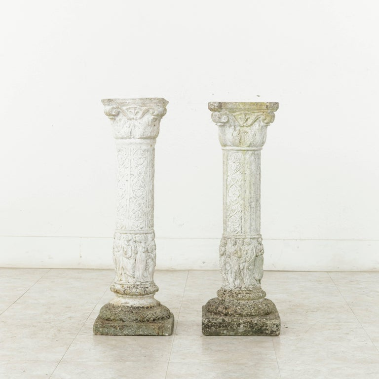 This pair of cast stone columns or pillars from the mid-20th century originally graced the gardens of a manor house in Normandy, France. Motifs of classical figures surround the base of the columns with interlaced rosettes above. A false pair, one