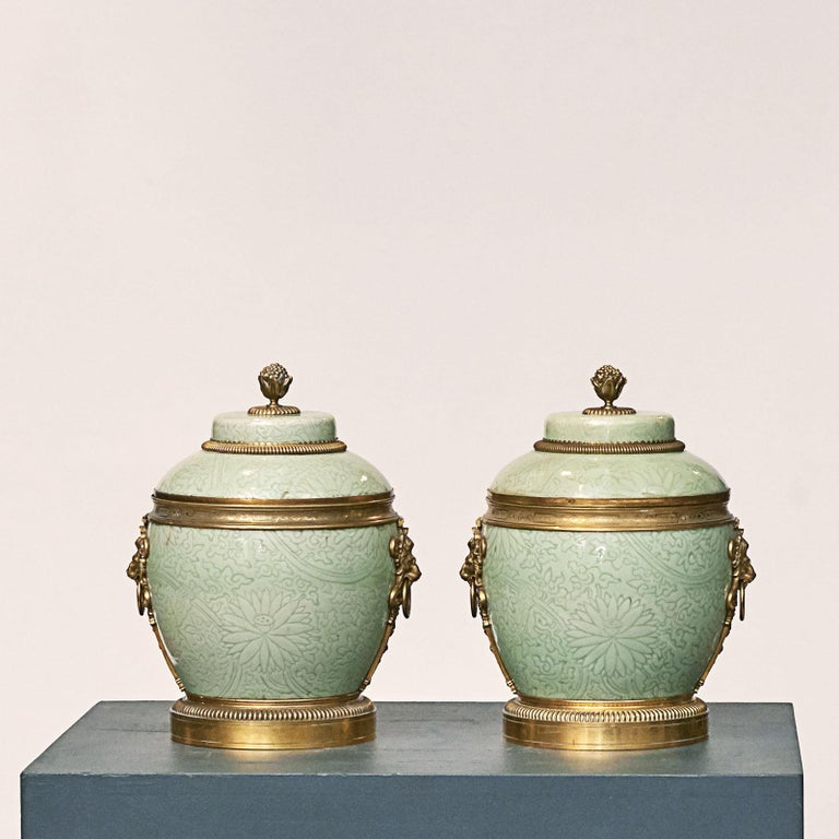 Pair of French lided vases, Celadon porcelain with gilded bronze fitting. Each with knob on lid in the shape of pomegranate, Each side with handles in shaoe of lion masks with ring. Marked inside lid