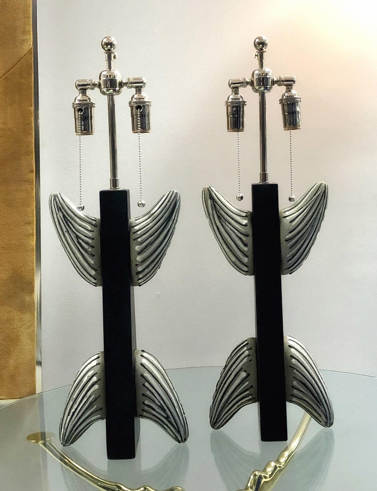 A pair of striking lamps. Black enameled wood with ceramic elements. New wiring.