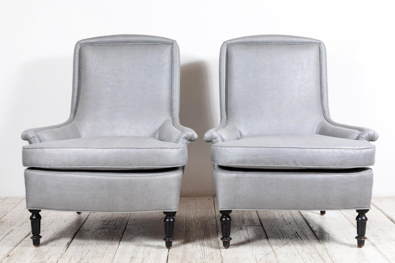 Pair of French club chairs with beautiful scrolled arms and unique piping details. Newly upholstered in grey beetled linen by Howe of London. Original turned black painted legs.