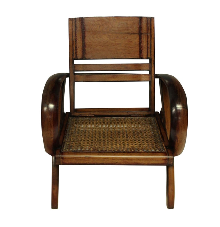 A pair of French Colonial Art Deco planter chairs, in stained teak, with cane seats. Vietnam.