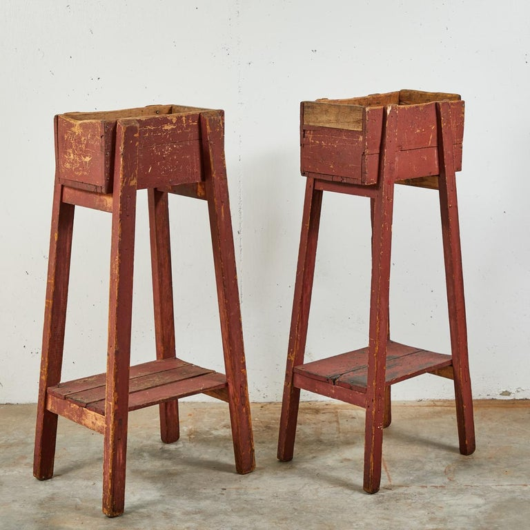Pair of French country red painted wooden planters on long splayed legs. Serves as a pedestal or plinth.