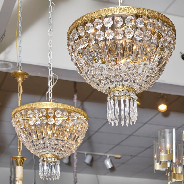 """Pair of French crystal chandelier flush mounts made of embossed gilt brass and crystal. The pair features a rich array of cut crystal """"cabochons"""" and pendants. They have been newly wired to fit US standards."""