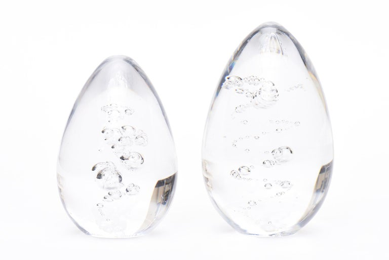 This pair of vintage French Daum signed crystal clear glass paperweights have bubble inclusions inside that are of a sculptural form. They are signed Daum France. They are two different sizes and make a great desk accessory the largest size is