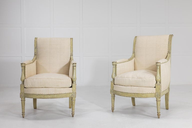 Pair of early 19th century French armchairs with wonderful faded original paint, finely carved decoration and upholstered in vintage linen.