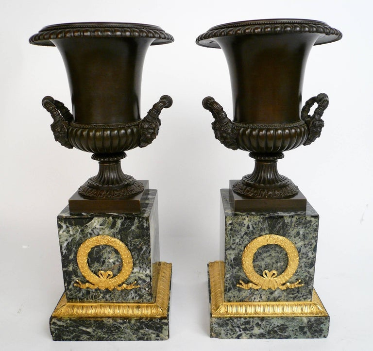 This handsome pair of urns feature neoclassical motifs, including acanthus leaves, egg and dart borders, and Bacchus mask handles. The Verde antico marble plinth bases are mounted with ormolu leaf and berry design wreaths.