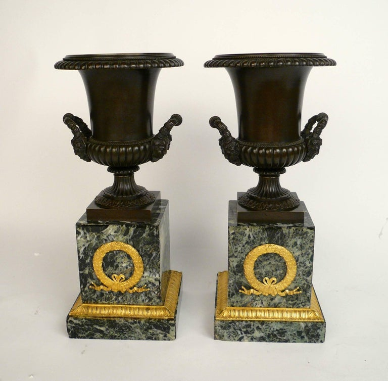 Patinated Pair of French Empire Bronze and Marble Urns For Sale