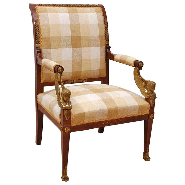 An exquisite pair of Empire armchairs/ fauteuils in fine mahogany with bronze dore´ ormolu mounts decorating the upper crest and lower back splat, with rosettes and palmettes on legs terminating with sabots of lions' paws and caryatids of winged