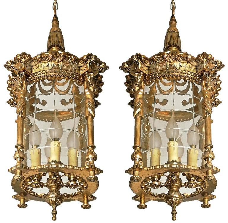 Beautiful pair of antique large French Empire caryatids cast bronze lanterns. Fire gilded solid heavy bronze and cut glass shade with four-light. Measures: Diameter 12 in/ 30 cm Height 32 in/ 80 cm Weight: 12 Kg / 25 lb/ each Four-light bulbs E-14 /