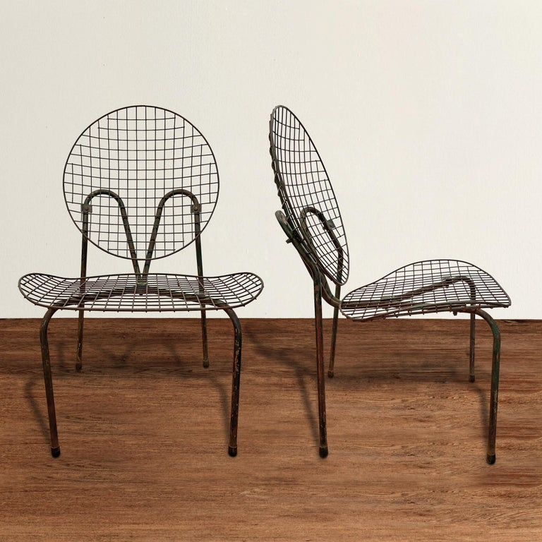 A chic and sculptural pair of early 20th century French garden chairs with bent tubular frames and wide wire mesh backs and seats. Chairs are perfectly comfortable as they are, but they would be beautiful with custom cushions as well. Also work