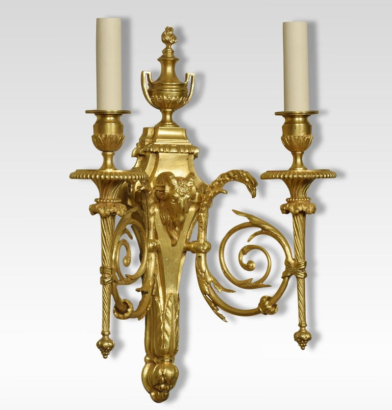 A pair of gilded bronze twin branch wall lights, the leaf scrolling arms with eagle-headed capitals having circular drip pans and acanthus sconces. Issuing from tapering backplate, with pierced finial above rams headed centre. The wall lights have