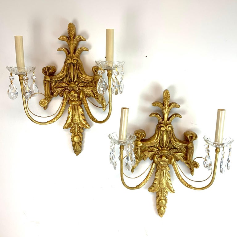 Pair of French giltwood and crystal wall sconces, each one fitted with two candelabra lights, with nicely carved cartouche backplate (17.5