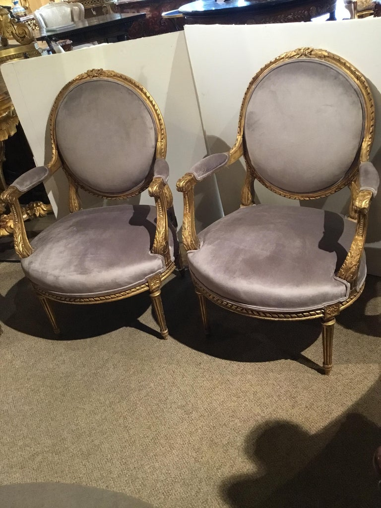 Oval back giltwood chairs with new designer fabric in gray hue. Reeded legs and the backs are carved with a bow carving at the crest. These chairs are sturdy and without problems.