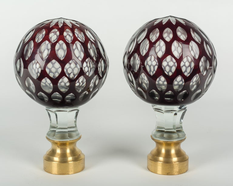 A pair of early 20th century French cut glass boules d'escalier, or newel post finials. Clear glass with an outer layer of deep ruby red and a multi-cut star at the top. These wonderful finials were used as decorative elements at the bottom of a