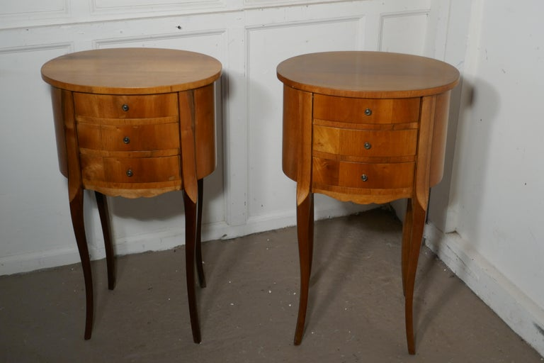 Pair of French golden cherry oval bedside cabinets  This is a pretty pair of cabinets or chevets, they are made in golden cherry and have an oval shape, they each have 3 drawers to the front and stand on splayed legs  The cabinets are in good