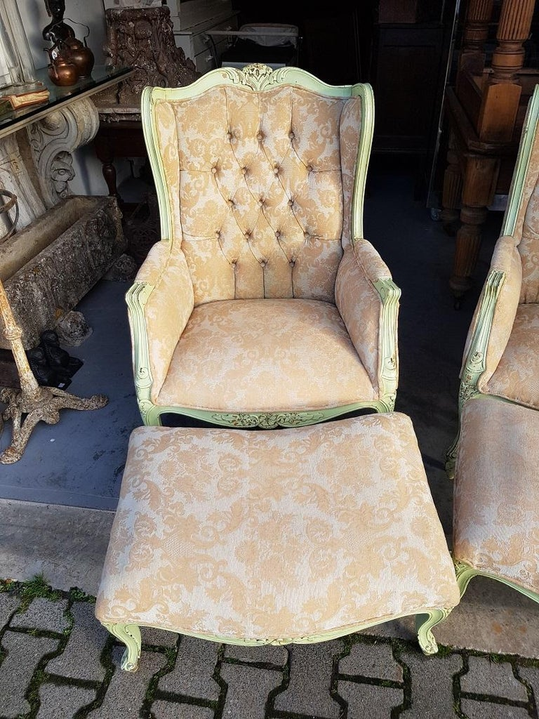 Set of 2 identical French green painted ear armchairs with matching footstool and everything is decorated with carvings in Louis XV style and equipped with Classic upholstery, all around in a good condition with light user marks. Originating from
