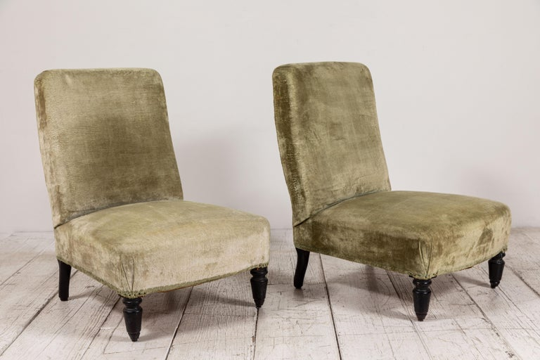 Pair of French Deco slipper chairs upholstered in original light sage green velvet. Original dark turned legs adds to the vintage charm.