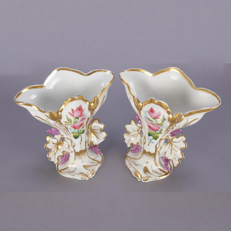 A pair of antique French porcelain Old Paris spill vases feature floral form with hand painted and gilt floral and foliate decoration, circa 1880.  Measure: 9