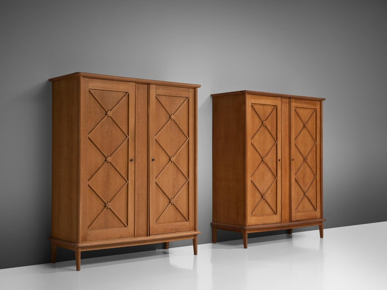 Pair of cabinet, oak, France, 1960s  An elegant case piece in oak that features geometric details in the doors. The high boards are lifted by slim, conical legs that give the solid looking body a more airy appearance. The cabinets offer plenty of