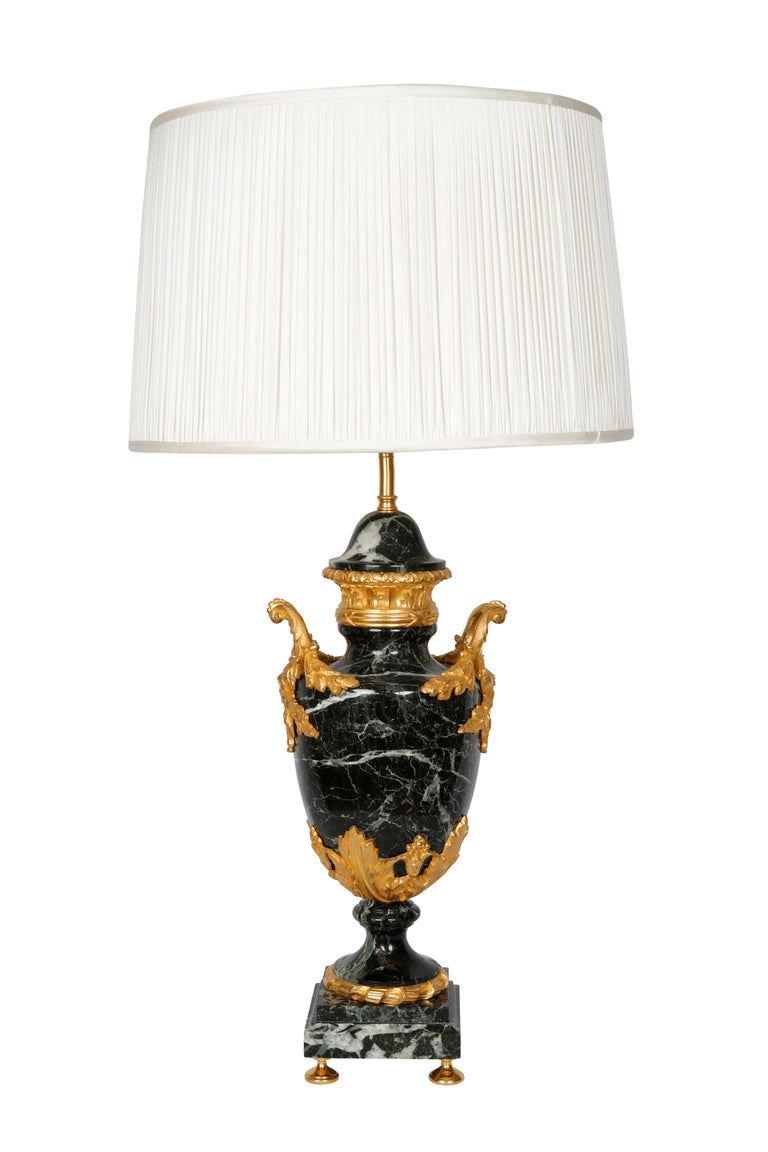 Crafted in France circa 1880, each cassolette is made of carved green marble and has a bronze base and decorative bronze mounts. The cassolettes have been converted into a table lamps and both have custom, pleated white shades. The lamps are in