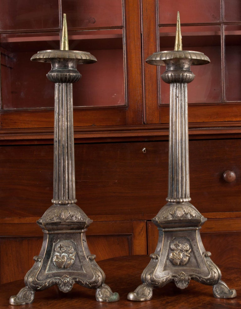 A magnificent pair of 19th century silver plate candlesticks from Catholic Church altar in France. The fixtures have column-form shafts that are topped in bobeches, and finished in ribbed and reeded designs. The bases are pyrimidal in shape, each