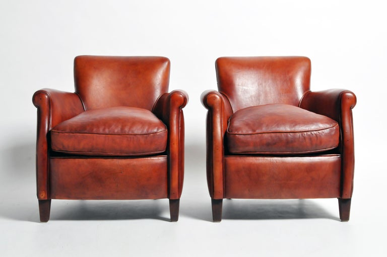 This pair of armchairs are from France and made from leather and wood, circa 21st century. They are newly made and feature a beautiful oxblood brown color; sturdy, comfortable, and ready for daily use.