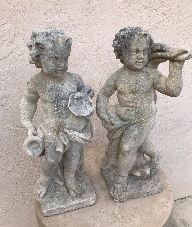 Charming pair of limestone French garden putti.