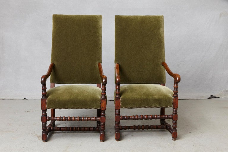 Striking pair of antique French Louis XIII walnut fauteuils or throne chairs with carved armrests, bobbin turned legs joined by H-shaped stretchers, nailhead trim, upholstered in green mohair, circa 1870s. The chairs are in excellent condition,