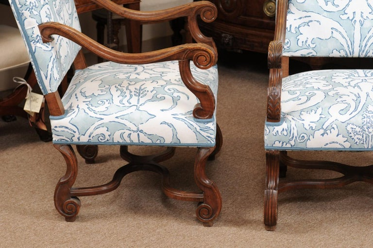 The pair of French Louis XIV style walnut armchairs/ fauteuils in pale blue/ off-white linen upholstery with high rectangular backs, carved down slept scrolled arms and carved mutton bone legs joined by X-stretcher.