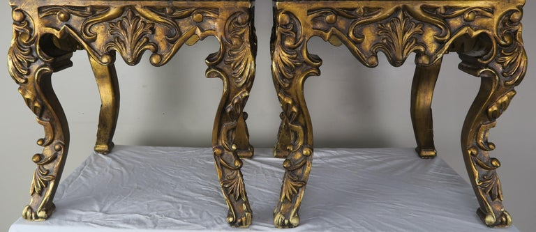 Pair of French Louis XV leather benches upholstered in brown colored leather with antique brass colored nailhead twin detail. Beautiful carving throughout the antique giltwood finish. The benches stand on four cabriole legs that are beautifully