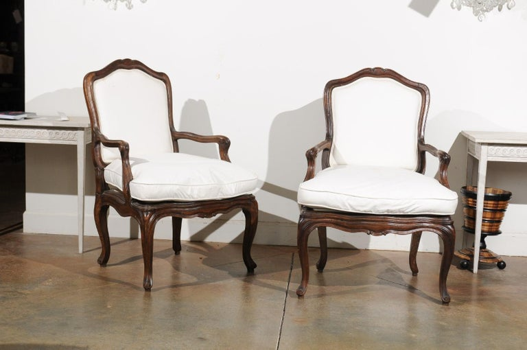 A pair of French Louis XV style walnut fauteuils from the early 19th century, with double welt upholstery and cabriole legs. Born in France during the Restauration period, each of this pair of armchairs features a slightly slanted back topped with a