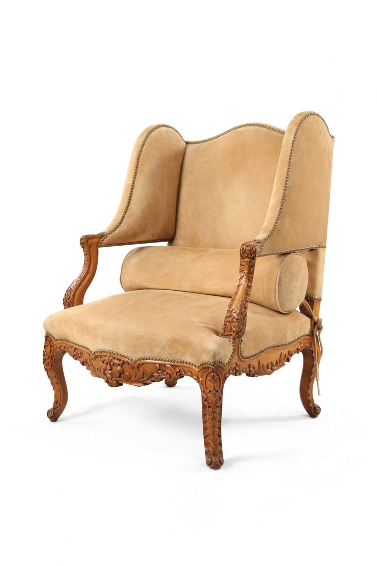 Pair of French Louis XV style (19th century) wing back open armchairs with an open lower back section beige suede upholstery, carved wooden arms and frames, and brass upholstery nail detail.