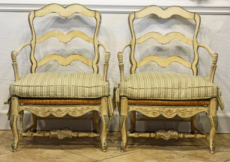 These attractive French carved bergere chairs in the Louis XV style of generous proportions feature beautifully hand carved frames painted antique white with pale green accents supporting rush seats in the French Provincial tradition. The surfaces