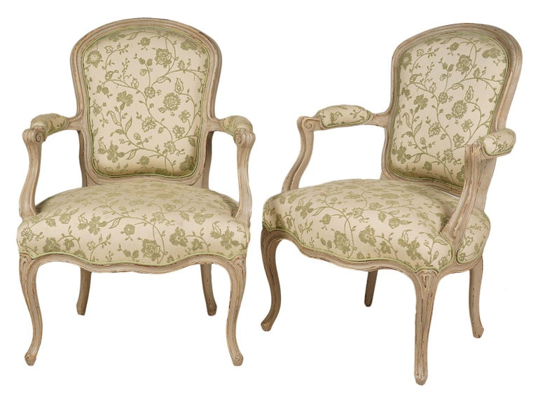 This pair of French Louis XV style armchairs, dating to the early 20th century, feature carved and painted frames, upholstered seats and back rests newly covered with a tasteful fabric.