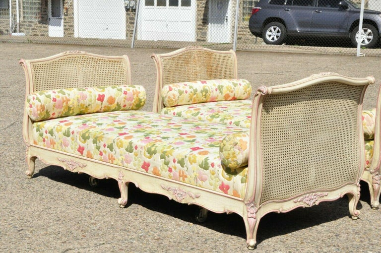 Pair of antique French Louis XV style pink and cream painted carved wood & cane daybeds. Item features double cane foot and headboards, pink and cream painted finish, solid wood frame, cabriole legs, quality craftsmanship, great style and form,