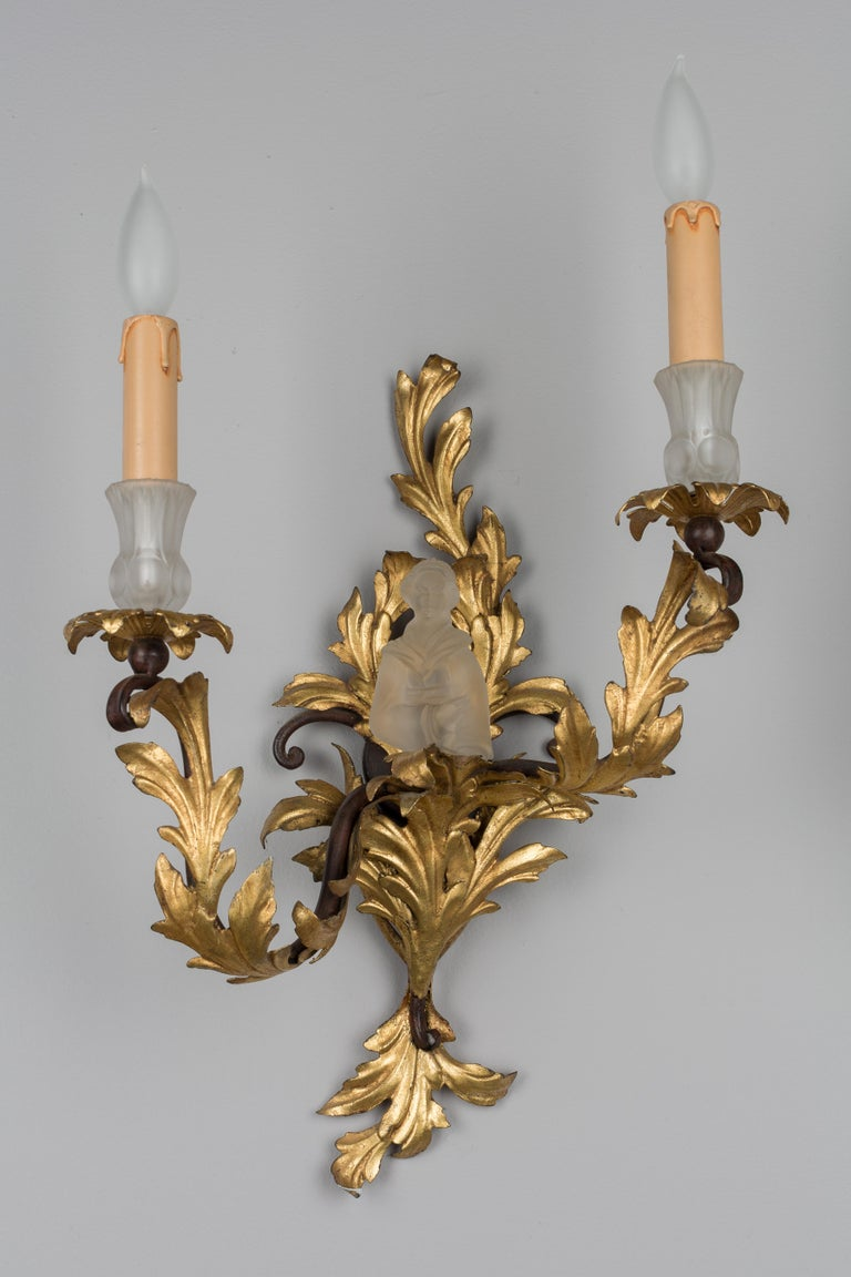 A pair of French Louis XV style tole doré sconces, each featuring two candle arms with scrolling foliage motif. Unusual glass bobeches and a Lalique style Japanese figure that fits into the centre. In excellent condition with bright gilt. Wired with