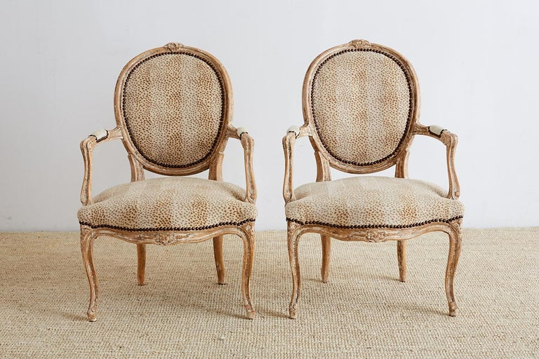 Fabulous pair of French Louis XV style carved fauteuil armchairs. Featuring an animal print upholstery with a linen inset in the exposed back. The frames have floral carved crests and aprons with molded arms and legs. The upholstery is bordered with