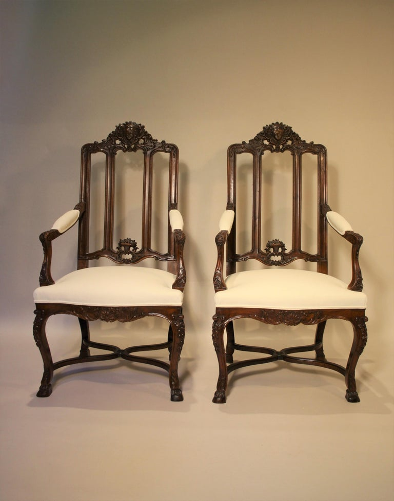 Exceptional pair of 19th century French walnut armchairs. They are richly sculpted with acanthus leaves, shells, and a head of a goddess. These chairs were made in a Parisian Workshop and come from the Castle of Fanson in the Belgian Ardennes (About