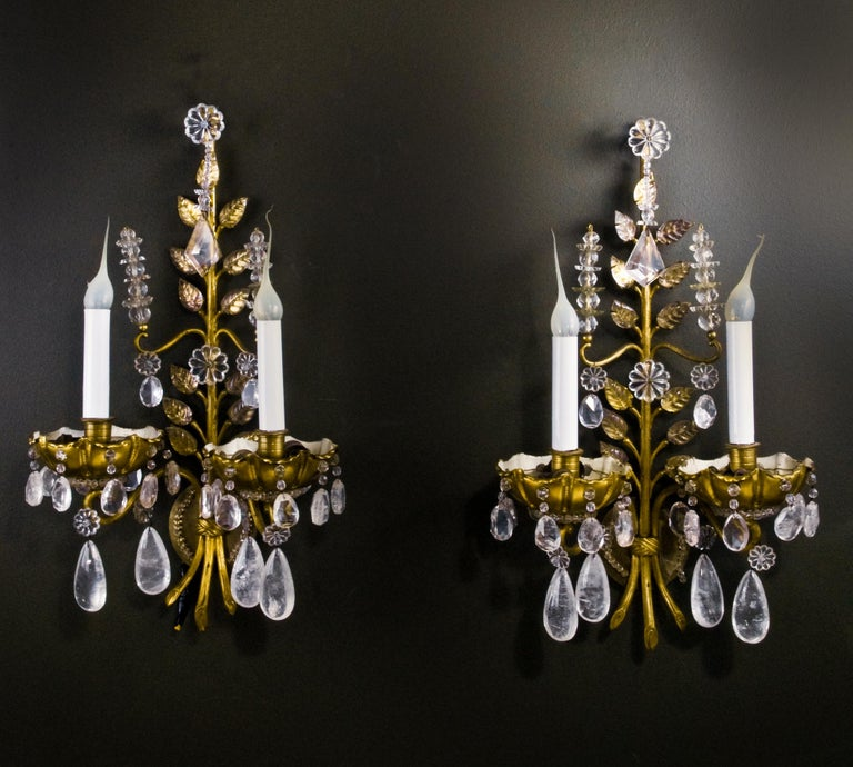 A pair of fine French Louis XVI Baguès style rock crystal, glass and gilt bronze double light wall sconces embellished with rock crystal prisms, glass beads and glass leaves.