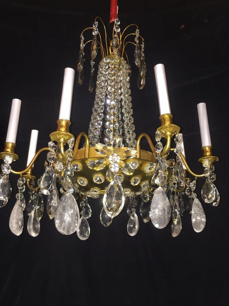 A pair of unusual antique French multi light gilt bronze, cut rock crystal and crystal chandeliers of fine detail embellished with rock crystal prisms, large crystal flowers and cut crystal chains further adorned with a central gilt bronze dish in