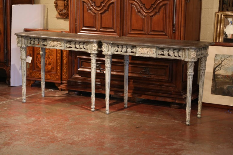 This elegant pair of antique, painted consoles was crafted in the southwest part of France using old elements. Each table features four tapered legs with acanthus leaves at the bottom, round corners with flowers medallions and delicate carvings