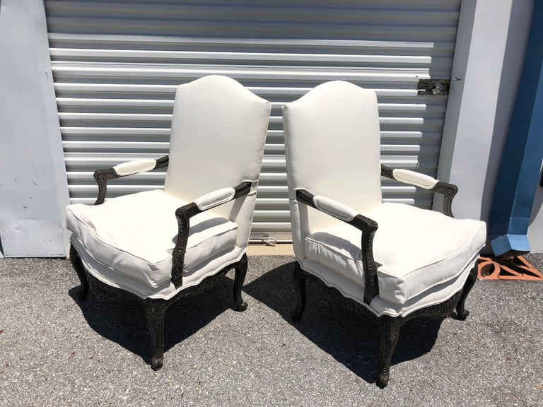 This pair of French style armchairs have carved legs, front and side panels finished in black lacquer. They have been newly upholstered having a separate cushion filled with down and rapped cushion inside (very comfortable)