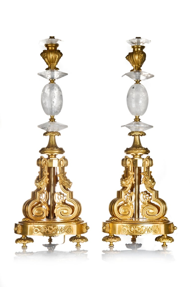 A pair of spectacular French Louis XVI style tall cut rock crystal and gilt bronze lamps embellished with flowers and figural masks.