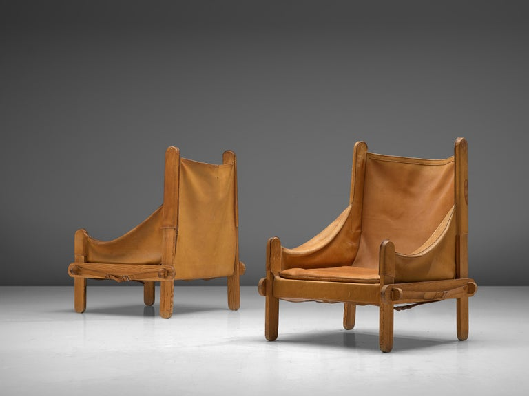 Pair of lounge chairs, leather, wood, metal, France, 1950s  These lounge chairs are characterized by the patinated cognac leather that is adjusted to the wooden frame consisting of wooden slats with round ends. The warm colored leather is attached