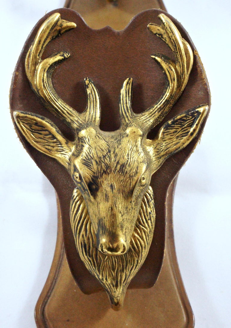 Pair of French mid brown leather and brass gun racks with a beautiful detailed deer design, the deer have a lovely black patina finish. The racks have one eyelet on each rack for wall mounting, and a metal rod on each rack at the back which is