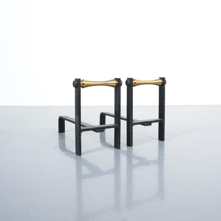 Pair of French midcentury andirons from iron and brass. Elegant French andirons made from forged iron with brass details. Good condition with signs of rust on the wrought iron parts (the base for the wood). Dimensions: 12.59