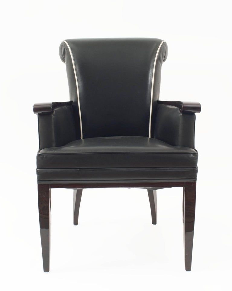 Pair of French mid-century dark rosewood stained bergere armchairs with a rolled back and carved scroll arm upholstered in black leather with white piping (by Jean Pascaud).   Jean Pascaud was born in Rouen in 1903. He took a degree in engineering