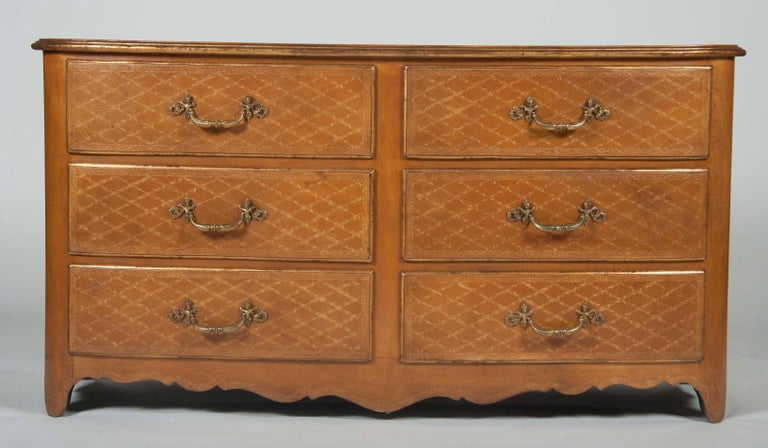 Handsome and elegant pair of large-scale French Louis XVI style leather wrapped commodes with bronze mounts. These impressive chests are covered in leather with tooled gilt diamond pattern decoration. Very fine craftsmanship. Mid-20th century.   Can
